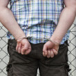 Man in handcuffs behind wire fence — Stock fotografie