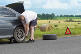 Man changing tire on the road — Stock Photo