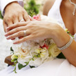 Hands and rings on wedding bouquet — Stock Photo #12359292