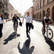 Businesspeople riding on bikes and running in city — Stock Photo