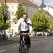Young businessman riding a bicycle in the city — Stock Photo