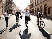 Gens d'affaires à cheval sur les vélos et en cours d'exécution dans la ville — Photo