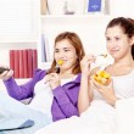 Teenage girls watching tv and eating fruit salad — Stock Photo