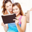 Two happy teenage girls using touchpad computer — Stock Photo #11797742