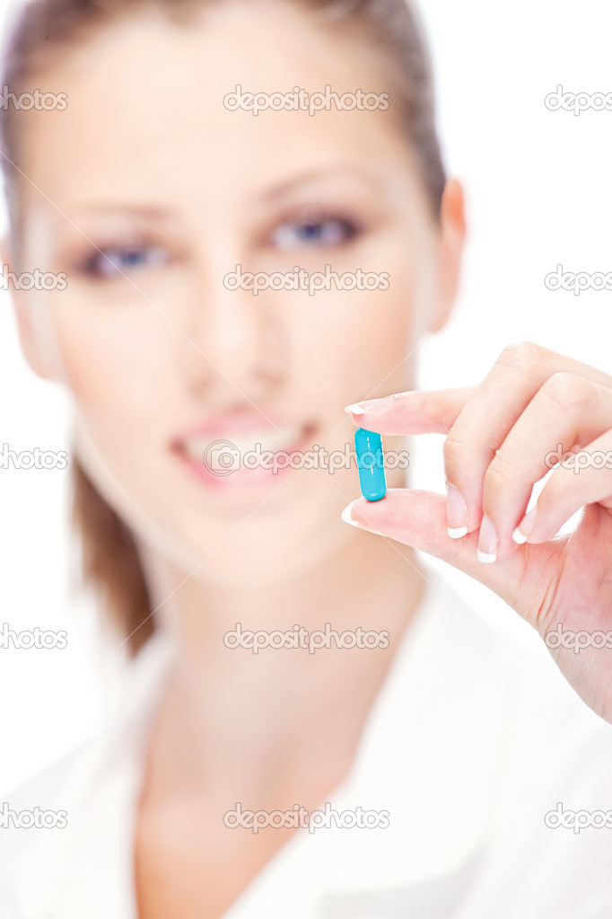 Pretty female nurse holding blue pill, focus on pill  Stock Photo #11861679