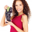 Happy brunette holding grape — Stock Photo