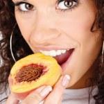 Woman eating peach — Stock Photo