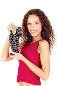 Happy brunette holding grape — Stock Photo