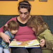 Mother with kids reading a book — Stock Photo
