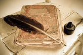 Old book, quill and black ink — Stock Photo