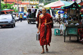 Young monk walking in Yangon with offering lunch — Stock Photo