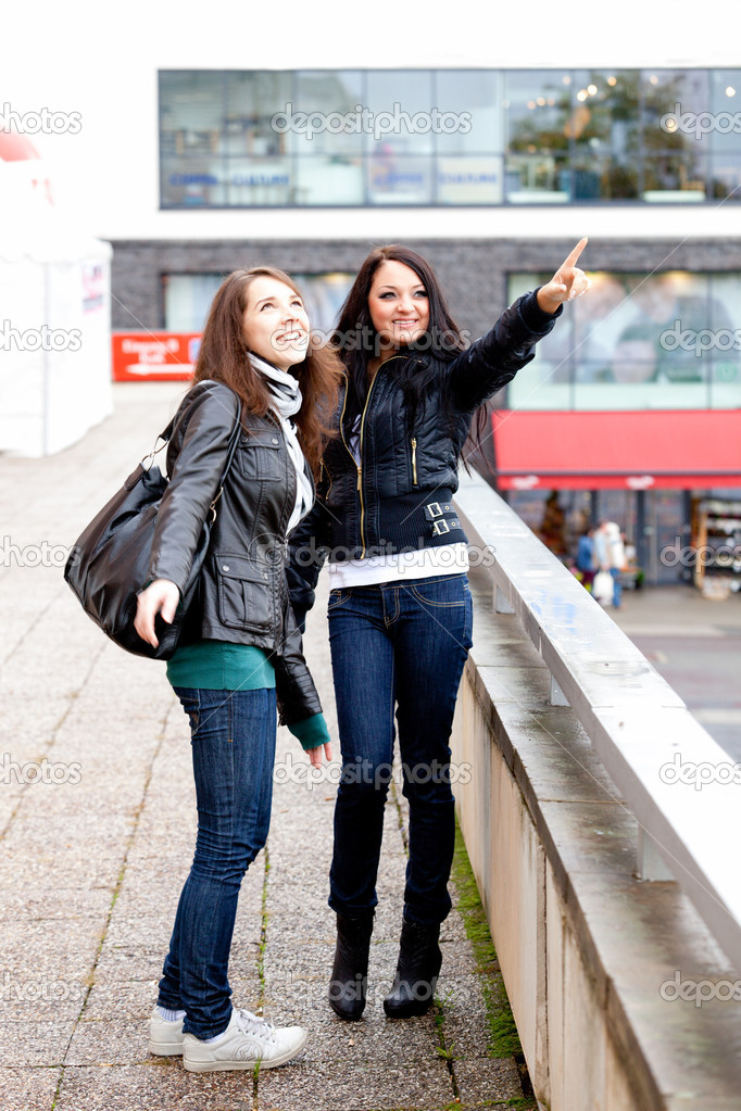 Two girls on walk in a city in the autumn, one points a finger on what that — Stock Photo #10953092