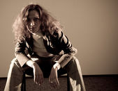 Donna seduta sulla sedia e guardando la telecamera — Foto Stock