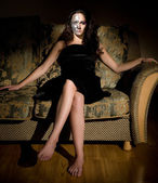 Two-faced woman sitting on the sofa — Photo