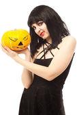 Woman in black dress holding a Jack-o'-lantern — Stock Photo