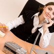 Businesswoman calling by phone at office - Stock Photo