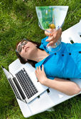 Woman lying on the lounge and holding a wineglass with a banknot — Stock Photo