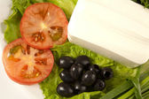A plate of cut tomato, olives, lettuce and feta cheese — Stock Photo