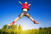Boy jumping against the blue sky — Stock Photo