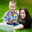 Smiling Mother and son laying on grass with laptop — Stock Photo