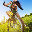 Woman wiht bike standing against the blue sky - Stock Photo