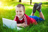 Smiling boy sitting with a laptop on the grass — Stock Photo
