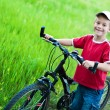 Stock Photo: Boy leads his bike on footpath