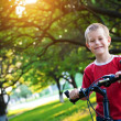 Funny  boy rides a bicycle in the park — Stock Photo