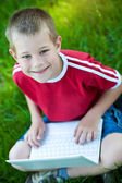 Six year old boy sitting with a laptop — Stock Photo