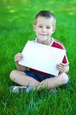 Boy on green meadow with a white sheet of paper — Stock Photo