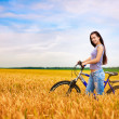 Girl with a bicycle on the wheat field — Stock Photo