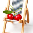 Couple in love.red cherryes on the beach chair — Stock Photo