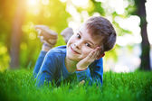 Cheerful little boy laying on the grass — Foto de Stock