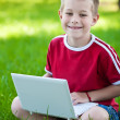 Boy sitting with a laptop on the grass — Stock Photo
