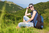 Girl is resting sitting on the grass in mountains — Stock Photo