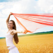 Girl with a red cloth catches wind in the yellow field — Stock Photo
