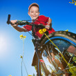Boy with bike standing against the blue sky — Stock Photo #11732455