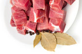 Pieces of frozen meat with laurel leaves isolated — Stock Photo