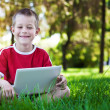 Boy sitting with a laptop on the grass — Stock Photo #12029716