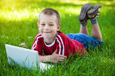 Six-year boy lying with a laptop on the grass — Stock Photo