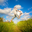 Stock Photo: Womjumping over blue sky