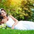 Royalty-Free Stock Photo: Happy bride in white dress lying on green grass