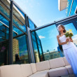 Royalty-Free Stock Photo: Bride with a bouquet on modern building background