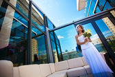 Bride with a bouquet on modern building background — Stock Photo