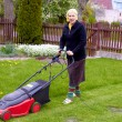 Senior woman working with lawn mower — Stock Photo
