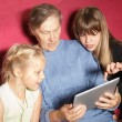 Two girls and grandmother using digital tablet — Stock Photo