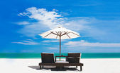 Beds and umbrella on a tropical beach — Stock Photo