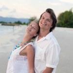 Attractive couple having fun on the sunset beach — Stock Photo