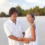 Attractive couple having fun on the sunset beach — Stock Photo #11047604