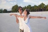 Coppia attraente avendo divertimento sulla spiaggia tramonto — Foto Stock